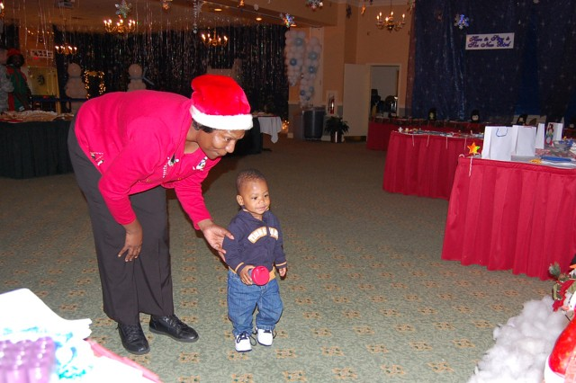 Linda Lesueur, FMWR, talks to her 16-month old grandson, Ethan Mason, about the Winter Wonderland display inside Hunter Club following the Hunter Christmas Tree lighting, Dec. 7.