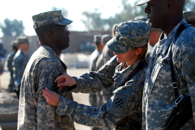 Major Sid Taylor, HHC, 2nd HBCT, 3rd ID, receives his combat patch from Capt. Leah Lato and 1st Sgt. Derrick Flowers, both from HHC, 2nd HBCT, 3rd ID, during 2nd Brigade's Combat Patch ceremony held at FOB Marez, Iraq, Dec 2.