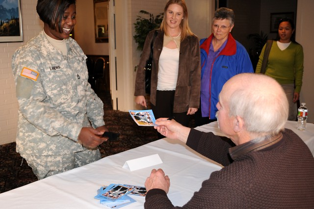 Sgt. 1st Class Latasha Lamons, Headquarters and Headquarters Company, 40th Military Police Internment and Resettlement Battalion, gets an autograph for her son from Dennis Leonard, former Kansas City Royals baseball player, Dec. 2 at the Frontier Conference Center, Fort Leavenworth, Kan. Royals Charities visited post to present a $25,000 to Army Community Service for deployed families.