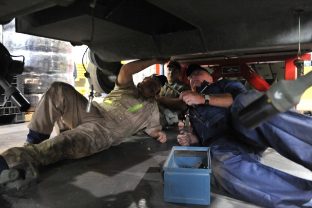 Anniston Army Depot mechanic Charles Armitage (right) works with two technicians from General Dynamics Land Systems, Phillip Kines and Daniel Huddleston, to install the differentials on a Stryker.