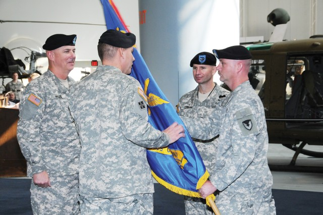 ACLC Sgt. Maj. John D. Eastburn hands outgoing ACLC commander Col. Alan M. Stull the unit colors at the U.S. Army Aviation Museum. Stull relinquished his command to fellow Embry-Riddle Aeronautical University ROTC graduate Col. Richard E. Crogan II, middle, during a ceremony Monday.