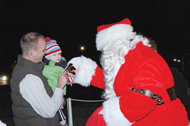Santa Claus greets 19-month-old Jameson and his father, 2nd Lt. Charles Ackley, of D Co., 1st Bn., 145th Avn. Regt., Dec. 3 at the annual post Christmas tree lighting ceremony. Hundreds of community members gathered for hot drinks, holiday carols and fellowship during the annual event.