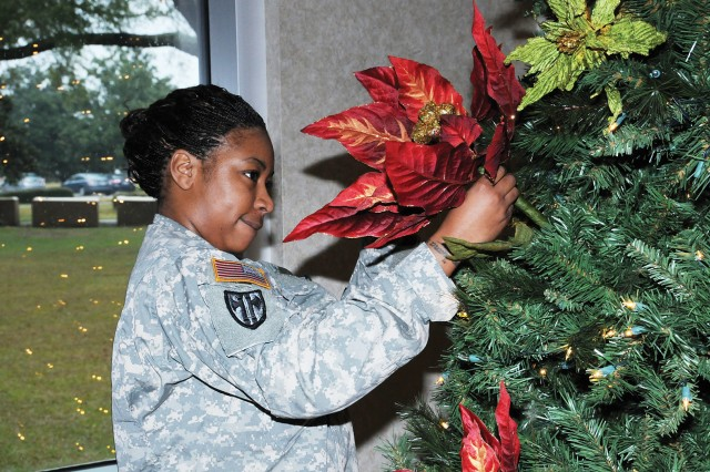 Spc. Ivorie Peagler, Secretary of the General Staff supply specialist, arranges decorations on a towering evergreen located in the headquarters building Tuesday.