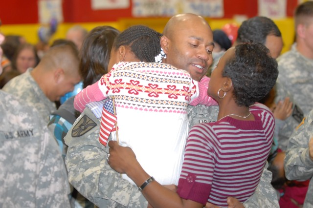 1st Lt. Will Harris hugs his wife, Sgt. 1st Class Catherine Harris and 5-year-old daughter, Taryn, after the homecoming ceremony for the 699th Maintenance Company on Dec. 10, 2009 at Fort Irwin, Calif. The unit returned from a yearlong deployment to Iraq.