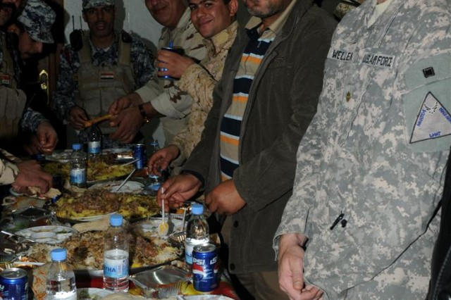 Iraqi Soldiers, Iraqi Police and Coalition forces dine together in the dining facility of the newly constructed Iraqi Army Camp Al Memona, Iraq, shortly after the ribbon cutting ceremony celebrating the official opening of the new base Dec. 9.