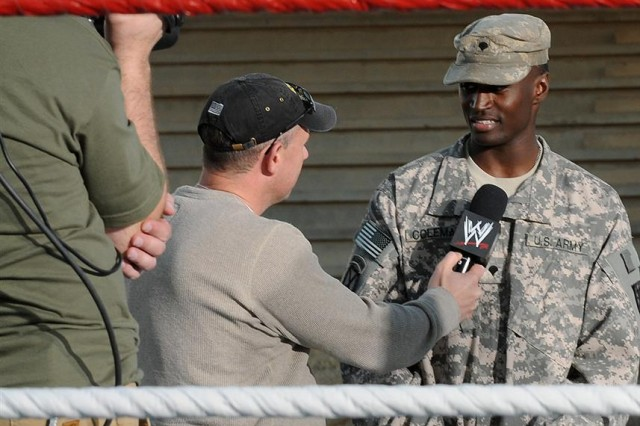Spc. Quinton L. Coleman, a cargo specialist with the 159th Seaport Operations Company, 80th Ordnance Battalion, 15th Sustainment Brigade, 13th Sustainment Command (Expeditionary), is interviewed by World Wrestling Entertainment staff after singing the national anthem and winning a contest Dec. 3 at Holt Stadium to open for a WWE match at Joint Base Balad, Iraq. Coleman, a Memphis, Tenn., native, sang with two partners at the WWE event Dec. 4.