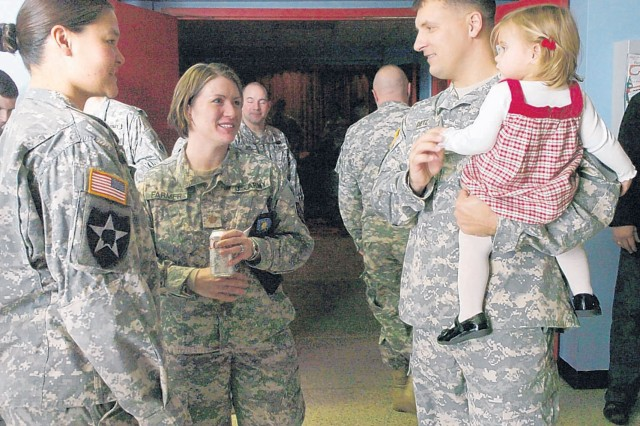 Capt. David Dietz Headquarters and Headquarters Command - Special Activities commander holds his 16-month-old daughter Kaedynce as he greets Soldiers after the change of command ceremony Monday at Wood Theatre. Dietz took command from Capt. Andrea So.