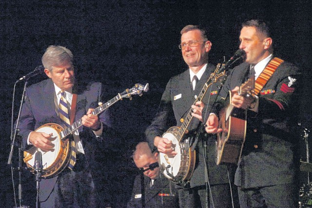 "FORT BELVOIR, Va. -- The Navy's Country Current, a bluegrass and country music ensemble, perform one of many holiday songs Friday evening at Wallace Theatre. Doug McKelway, guest banjo player accompanies Senior Chief Musician Keith Anderson and 1st Class Musician Kenny Ray Horton on ""Here Comes Santa Claus."""