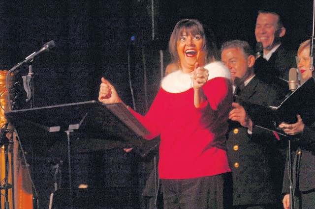 FORT BELVOIR, Va. -- Lisa Baden, WTOP radio personality dances along to the music Friday evening. The Navy's Country Current and Sea Chanters performed a holiday program at Wallace Theatre.