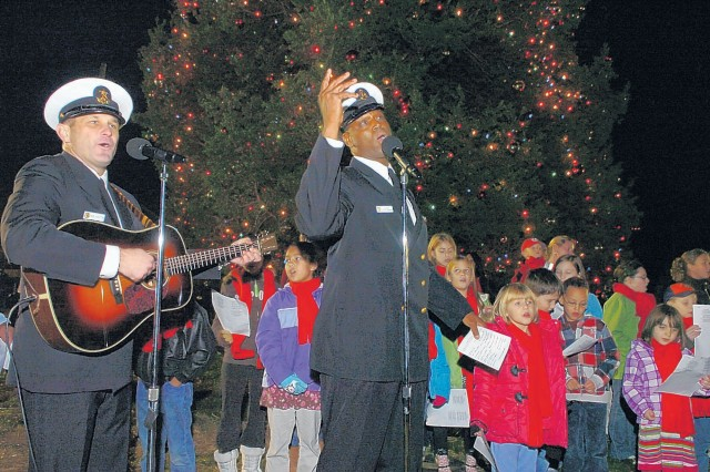 FORT BELVOIR, Va. -- The Navy's Country Current adds voices to the holiday songs performed by the childrens choir Friday at the Holiday Tree lighting at Belvoir Chapel.