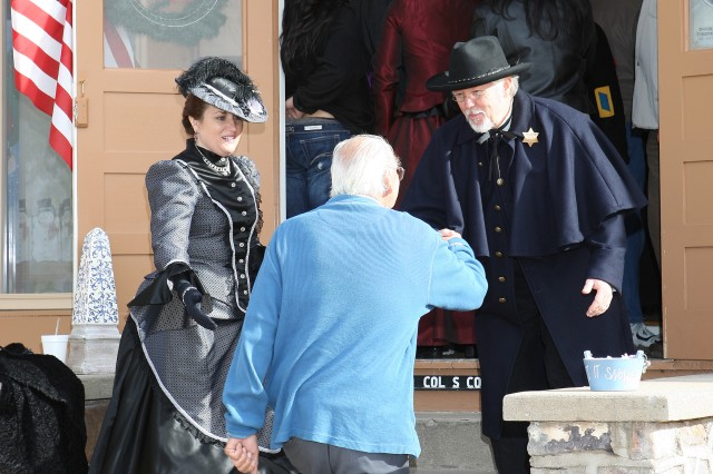 From left, Tombstone Vigilantes Melany Edwards-Barton and Jeff Ingertson help visitors up the stairs at the Wilder House during Sunday's Tour of Historic Homes. The Wilder House, built in 1884, was one of the 14 open homes that drew a crowd and helped the Fort Huachuca Community Spouses Club raise money for scholarships and other community projects.