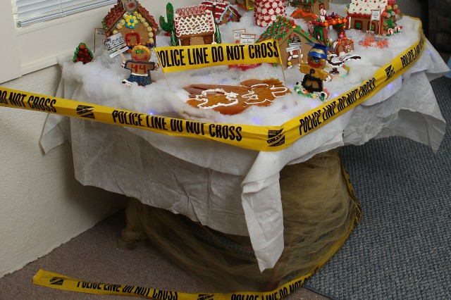 "The ginger bread house ""crime scene"" was crafted by the 111th Military Intelligence Brigade coffee group at Fort Huachuca. The family dog ate the ""parents"" of the two gingerbread children prior to the tour, prompting the quick change of a gingerbread family exhibit to a ""crime scene."""