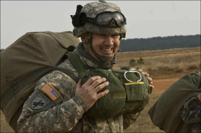 A smiling Maj. Gen. David N. Blackledge, commanding general of U.S. Army Civil Affairs and Psychological Operations Command (Airborne), walks off Sicily Drop Zone carrying his parachute during the 12th Annual Randy Oler Memorial Operation Toy Drop, Dec. 6, at Fort Bragg. USACAPOC(A) hosts the airborne operation with the support of Fort Bragg's XVIII Airborne Corps and Pope Air Force Base's 43rd Airlift Wing. Over 900 Soldiers donated a toy for a lottery ticket for the chance to jump under an international jumpmaster in order to earn either German or Canadian jump wings this year. The operation gives Soldiers and Airmen the opportunity to help local families in need over the holidays while boosting morale and incorporating valuable training. Since its inception, Operation Toy Drop has collected and distributed more than 30,000 toys for families of Soldiers as well as orphanages in the local community.