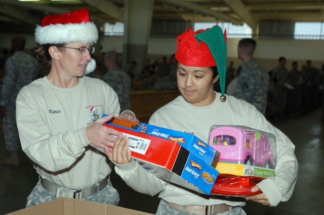 Sgt. 1st Class Catherine Reese and Spec. Melissa Menchaca, information security specialists for the U.S. Army Civil Affairs & Psychological Operations Command (Airborne), collect toys during Operation Toy Drop Dec. 4 on Pope Air Force Base, N.C.  The toys, donated by Fort Bragg paratroopers, will go to children in need throughout the Fayetteville, N.C. community.