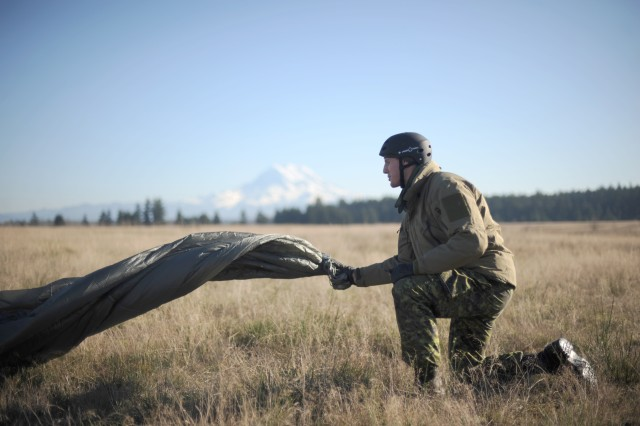 A Canadian special operations soldier packs up his parachute after jumping onto the Rogers drop zone on Fort Lewis, Wash., with U.S. 1st SFG Soldiers Dec. 2, during Menton Week.