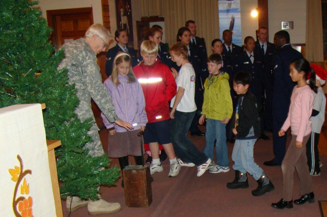 Col. Sandusky invited anyone in the audience under 10 and a-half years of age to come up to the front of the chapel to assist her by pushing the plunger in to light the tree.