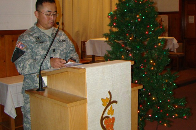Chaplain (Capt.) Martin Chang, who was the master of ceremonies for the tree lighting event, invites the attendees to join the Air Force Choir in singing traditional Christmas Hymns.