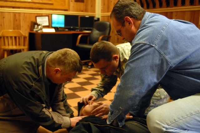 """Spc. Adam Coleman and Kirk Guin reenacted how they checked for a pulse and open airway while Linwood Young performed chest compressions. Sgt. Lee Quay was the """"choking victim"""" for the reeenactment."""