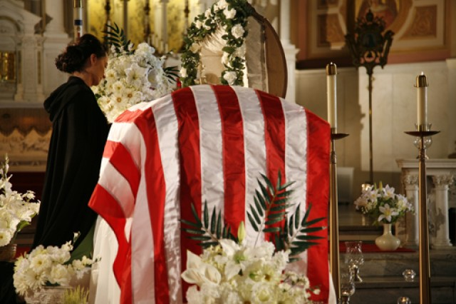 """Olivia"" (Margaret Lambos) stands grieving by the coffin of her husband (played by actor Mark Nillson) who was slain in battle.  Lambos, wife of HHB, 100th MDB (GMD) commander, Capt. George Lambos, plays the part of the widow in the award winning movie short, ""Last Dance."" Photo by Dorota Szalkowski, reprinted with permission of Aleksandra Hodowany"