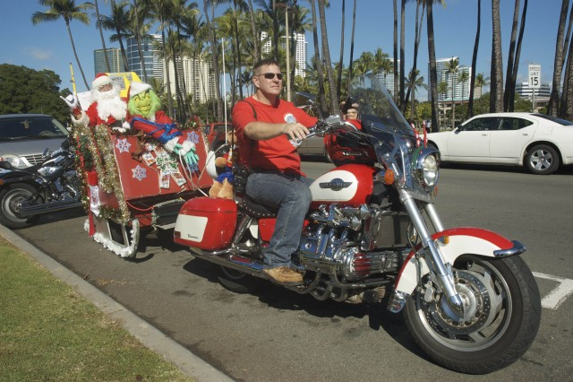 HONOLULU -- Master Sgt. Charles Owens, first sergeant, 305th Mobile Public Affairs Detachment, 9th Mission Support Command, gets ready to pull a sleigh carrying Santa (Fred Chang), the Grinch, dozens of presents and 500 lights, from Magic Island to Kapiolani Community College, during the 35th Annual Street Bikers United Hawaii Toy Run Parade, Dec. 6. Thousands of bikers participated in the benefit, including those from Owen's club, the Hawaii Goldwing Road Riders Association.