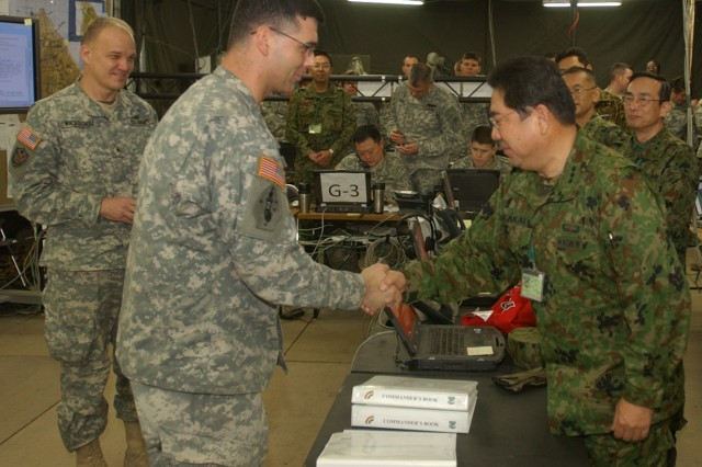 CAMP CHITOSE, HOKKAIDO JAPAN -- Lieutenant General Takeshi Sakai, commander of the Japan Ground Self Defense Forces' Northern Army, presents a commanders' challenge coin to New York Army National Guard Maj. Jamey Barcomb of the 42nd Infantry Division Headquarters Tactical Command Post #1. Barcomb, from Williamsville, N.Y. is the current operations battlestaff officer for the division command post. He provided Sakai with an overview of division command and control techniques and technology as part of Yama Sakura 57, the bilateral joint command post exercise here. Sakai is the codirector of the exercise. Looking on is Brig. Gen. Steven Wickstrom, the 42nd Infantry Division Commander. U.S. Army photo by Staff Sgt. Raymond Drumsta, 138th Public Affairs Detachment.