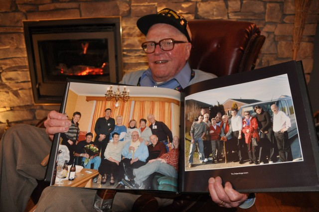 "World War II Veteran Everett ""Red"" Andrews displays a photo of a recent visit with the extended Goebles-Leroy family, with whom he has maintained a strong friendship since leaving their home after the Battle of the Bulge in 1945."