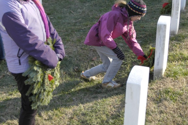 """Sam Thurston (left), 10, examines a grave marker where she will lay her wreath, while her friend, Bella Flowe, 12, places one beside her."""""""