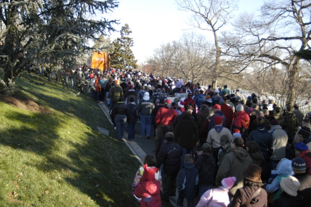 """Hundreds of people line up behind an 18-wheel truck to grab some wreaths to place around Arlington National Cemetery. Morrill Worcester, owner of the Worcester Wreath Company of Maine, has donated thousands of wreaths to be placed at the cemetery since 1992 and enlisted thousands more in his Wreaths Across America project."""""""