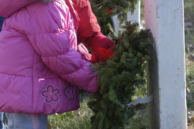 """Abbie Goodson, 2, places a wreath on a grave marker in Section Two of Arlington National Cemetery. Goodson, her parents, grandparents and eight other relatives and make the trek from Georgia to participate in the event. """"We hope to be back next year, and we'll bring even more Family out,"""" said Mike Goodson, Abbie's grandfather."""""""