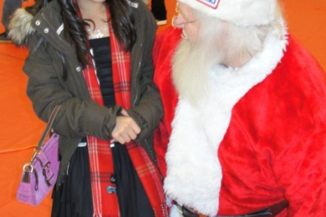 Kacie Basto, daughter of Major Adonis Basto, HHC 416th Theater Engineer Command, U.S. Army Reserve describes her wish list to Santa during the Chicago Bulls' Annual Christmas party for service members, their families and inner-city youth.