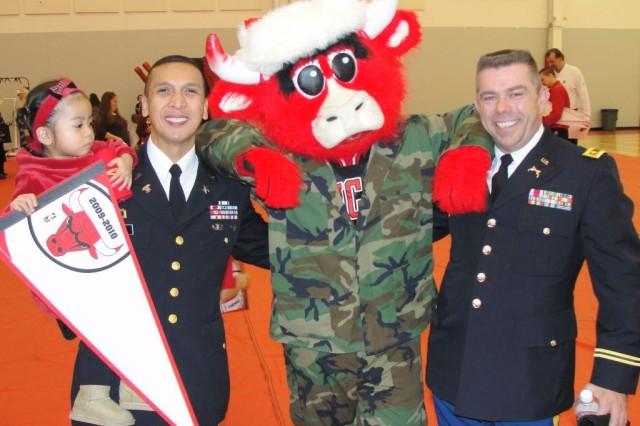 "Maj. Adonis Basto, his daughter and Maj. Bruce Townsend of HHC 416th Theater Engineer Command, U.S. Army Reserve, pose with the Chicago Bulls' mascot ""Bennie"" during the Bulls' Annual Christmas party for service members, their families and inner-city youth."