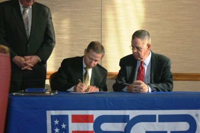 Paul L. Schiozza (center), President of AT & T Illinois, signs an Employer Support of the Guard and Reserve Statement of Support as James G. Rebholz (left), National Committee for Employer Support of the Guard and Reserve, and Assistant Secretary of Defense for Reserve Affairs, Dennis McCarthy, look on during a luncheon hosted by the Illinois Chamber of Commerce Board of Directors in Chicago Dec. 11.