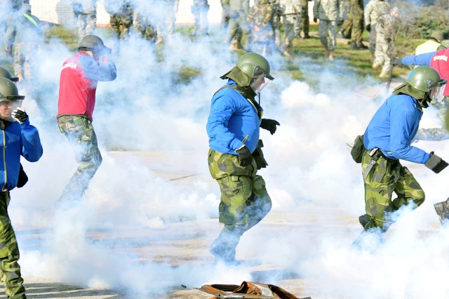 """Irish and Slovakian Army """"rioters"""" are forced back from their position by the use of """"tear gas"""" during recent training in crowd riot control."""