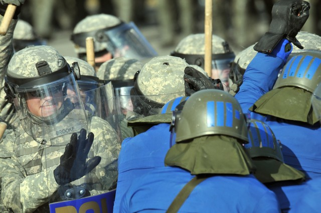 """Pfc. Remi Brooke, Grand Forks, a member of 2nd Platoon, Charlie Co., 231st Maneuver Task Force, helps hold the line against role-playing """"rioters"""" during recent crowd riot control training"""