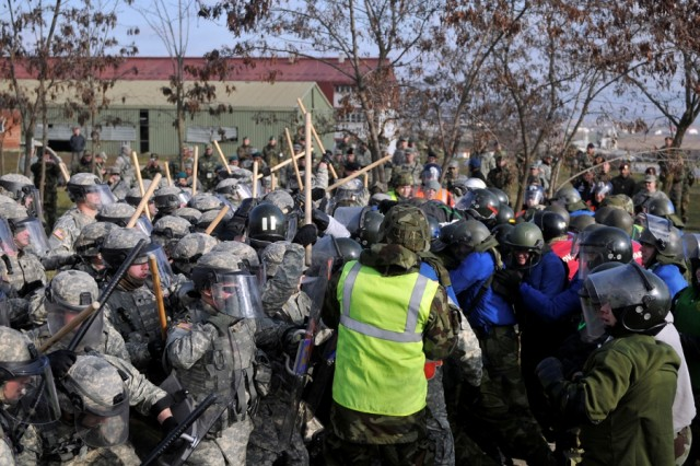 "Soldiers of 2nd Platoon, Charlie Co., 231st Maneuver Task Force engage role-players acting as rioters during recent training in crowd riot control. Soldiers from the U.S., French and Austrian militaries worked in cooperation to dispel the ""rioters"", who were from the Slovakian and Irish armies."
