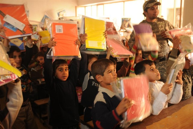 Children at the Al Waleed School hold up the school-supply kits delivered by U.S. and Iraqi Soldiers Dec. 6 during an Operation Back to School mission near Camp Taji, Iraq. Volunteers with the project collect school-supply donations and prepare kits to give to the schoolchildren in rural communities throughout Iraq