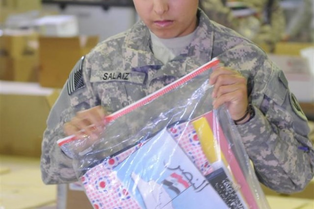 Spc. Cheryl Salaiz, a light wheel vehicle mechanic with the 623rd Quartermaster Company, 541 Combat Sustainment Support Battalion, 96th Sustainment Brigade, 13th Sustainment Command (Expeditionary) and a Las Cruces, N.M., native, packs school supplies Dec. 4 to make kits for schoolchildren near Contingency Operation Location Taji, Iraq. The kits will passed out to Iraqi school children during humanitarian missions conducted by volunteers with Operation Back to School.