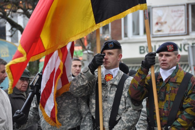 Adjudant Chef Henri Plessiet (right) becomes the first Soldier from the Belgian 1st Field Artillery Regiment to carry his nation's flag with the USAG Benelux Color Guard in the Battle of the Bulge anniversary parade in Bastogne. Sgt. Brandon McIntosh (left) carries the U.S. Flag.