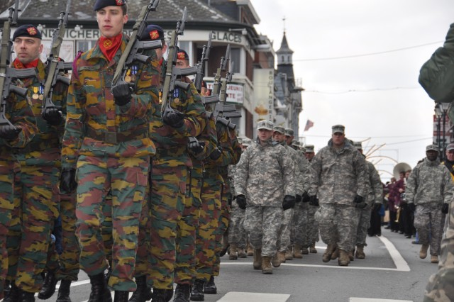 Headquarters Company, USAG Benelux, led by Capt. Eric Kuenke, follows the Belgian 1st Artillery Regiment in the annual Battle of the Bulge Parade through the streets of Bastogne, Belgium, Dec. 12, 2009.