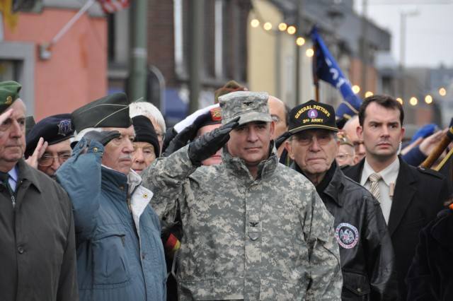 Marcel D'Haese, a Belgian WWII veteran from the 5th Fusiliers Battalion; Col. James Drago, commander, USAG Benelux; and Maurice Sperandieu, a Belgian WWII veteran who fought with Gen. George Patton's Third Army, salute the flag during the playing of the U.S. and Belgian national anthems at a 65th anniversary of the Battle of the Bulge commemoration in Bastogne on Dec. 12, 2009.