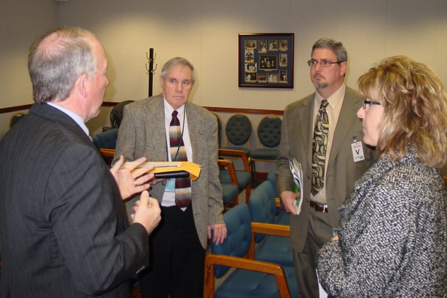 DSCC Deputy Commander James McClaugherty (left) answers questions from George Frye (left center), chief of Tobyhanna's Mission Materiel and Staging Branch, and Melissa Ross (right), chief of Tobyhanna's Commodity Processing Branch, as DSCC BRAC office chief Don Schulze (second from right) listens.