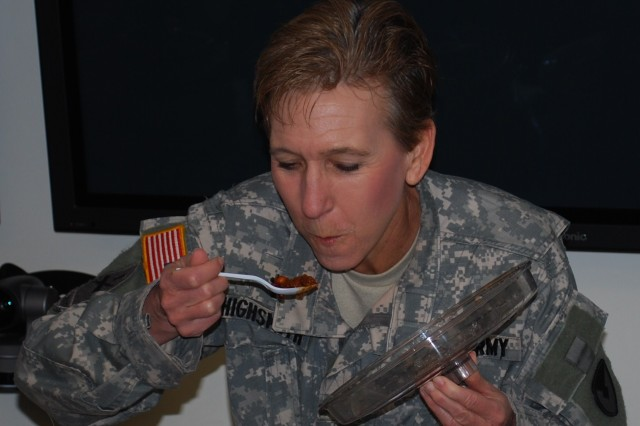One of three judges, Lt. Col. (Chaplain) Carol Highsmith, carefully prepares for another taste of chili.