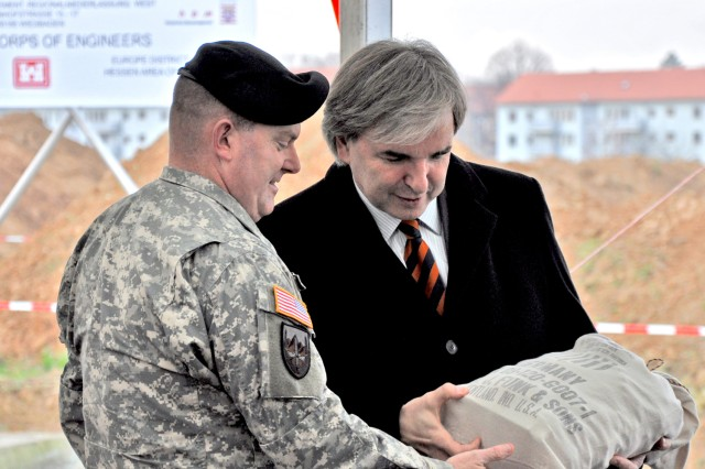 Wiesbaden Lord Mayor Dr. Helmut Mueller presents the Col. Jeffrey Dill, U.S. Army Garrison Wiesbaden commander, with a sack filled with chocolate during the ground-breaking ceremony. The original sacks were used to transport goods from the U.S. destined for Germans after World War II and during the Berlin Airlift.