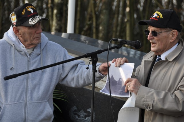 """Henry """"Hank"""" Skowronski (right) shares a photo taken by Carmen Gisi (left) on Dec. 20, 1944, of medical tents of the 326th Airborne Medical Company. Germans attacked the company during the Battle of the Bulge Dec. 19, 1944. Skowronski left the camera in his foxhole when he was captured after the attack. Gisi found it the next day when his unit, the 401st Glider Infantry Regiment, was called in for support. The two reunited for the first time in July 2009 and shared their story with citizens of the town Sainte-Ode 65 years later."""