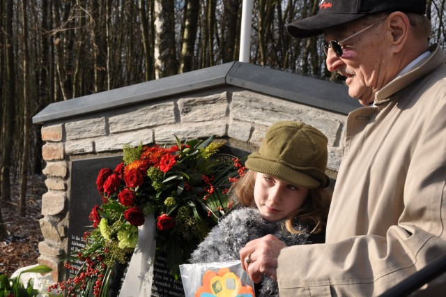 """A local Belgian girl presents a gift to World War II veteran Henry """"Hank"""" Skowronski at the unvieling of a new monument erected on the 65th anniversary of the Battle of the Bulge for the 326th Airborne Medical Company Dec. 13, 2009. Skowronski was stationed in Sainte Ode, Belgium, on Dec. 19, 1944, when his unit came under attack by the Germans. He was captured as a prisoner of war until the end of the war."""