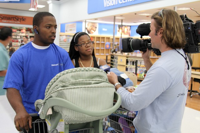 Spec. Cliff Flambert and his wife are interviewed by a local television station before heading through the isles of Walmart.