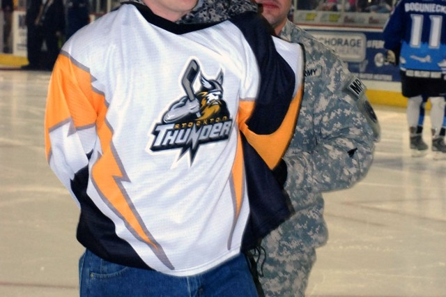 Sgt. Kyle Mahaffey, left, of Fort Richardson's 28th Military Police Detachment, is escorted off the ice by Staff Sgt. Ryan Hastings, 28th MP Det., after posing as a member of the Stockton Thunder who stole the puck prior to the Alaska Aces Military Appreciation Game Dec. 11 at the Sullivan Arena in Anchorage, Alaska.