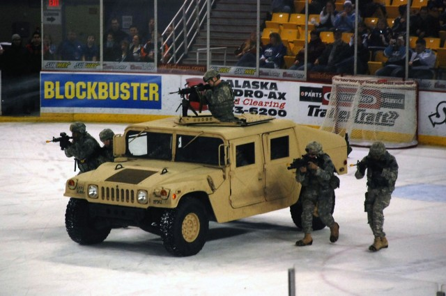 Soldiers with Fort Richardson's Military Police Battalion roll onto the ice in support of the Coast Guard, Marine Corps and Alaska Army National Guard during a mock search and destroy mission Saturday during an intermission of an Alaska Aces Military Appreciation Game at the Sullivan Arena in Anchorage, Alaska.