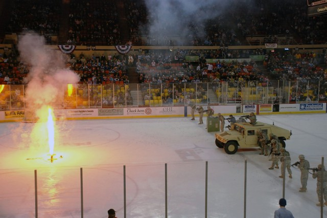 U.S. Army Alaska Soldiers take center ice alongside members of the Coast Guard, Marine Corps and Alaska Army National Guard during a mock search and destroy mission Dec. 12 during an intermission of an Alaska Aces Military Appreciation Game at the Sullivan Arena in Anchorage, Alaska.