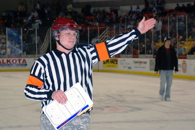 Master Sgt. Marc Fox, Arctic Military Police Battalion, acts as a referee during an all services obstacle course Dec. 11 at an Alaska Aces Military Appreciation Game at the Sullivan Arena in Anchorage, Alaska.""